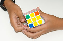 Κινητός κύβος Rubik ` s σε ένα άσπρο υπόβαθρο με την πείρα Και χ Στοκ Φωτογραφία