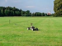 Κινητός ψεκαστήρας σε ένα κενό γήπεδο ποδοσφαίρου στην επαρχία στον ξηρό θερινό χρόνο στοκ φωτογραφία με δικαίωμα ελεύθερης χρήσης