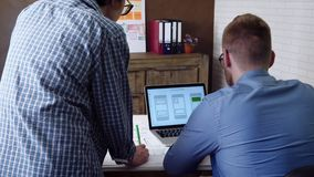 Κινητός app υπεύθυνος για την ανάπτυξη που σκιαγραφεί το σχέδιο νέο app και του συναδέλφου του που εξετάζουν την εργασία του απόθεμα βίντεο