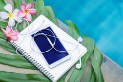 Κινητό έξυπνο τηλέφωνο με τα ακουστικά, βιβλίο σημειώσεων, λουλούδια frangipani plumeria Στοκ Εικόνες