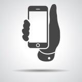 Κινητό εικονίδιο τηλεφωνικών διαθέσιμο χεριών σε ένα γκρίζο υπόβαθρο ελεύθερη απεικόνιση δικαιώματος