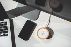 Κινητό τηλέφωνο και ασύρματος φορτιστής στον πίνακα γραφείων στοκ εικόνα με δικαίωμα ελεύθερης χρήσης