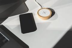Κινητό τηλέφωνο και ασύρματος φορτιστής στον πίνακα γραφείων στοκ φωτογραφία με δικαίωμα ελεύθερης χρήσης