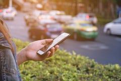 Κινητό τηλέφωνο λαβής γυναικών εκτός από το δρόμο στοκ εικόνες