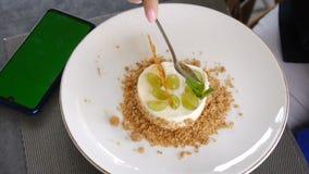 Κινητό τηλέφωνο με μια πράσινη οθόνη σε έναν καφέ Ένα χέρι παίρνει μια φέτα cheesecake με τα σταφύλια Ένα φλιτζάνι του καφέ απόθεμα βίντεο