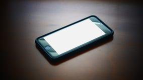 Κινητό τηλέφωνο με την άσπρη κενή οθόνη στο ξύλινο γραφείο στοκ φωτογραφία με δικαίωμα ελεύθερης χρήσης