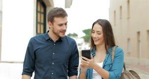 Κινητό τηλέφωνο ξεφυλλίσματος περπατήματος ζεύγους στην οδό απόθεμα βίντεο