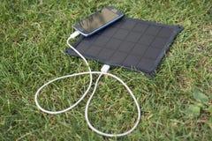 Κινητό τηλέφωνο που χρεώνει με τη ηλιακή ενέργεια - φορτιστής Στοκ Εικόνες