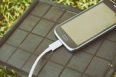 Κινητό τηλέφωνο που χρεώνει με τη ηλιακή ενέργεια - φορτιστής Στοκ εικόνα με δικαίωμα ελεύθερης χρήσης