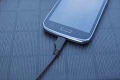 Κινητό τηλέφωνο που χρεώνει με τη ηλιακή ενέργεια - φορτιστής Στοκ Φωτογραφίες