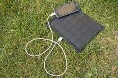 Κινητό τηλέφωνο που χρεώνει με τη ηλιακή ενέργεια - φορτιστής Στοκ Εικόνα