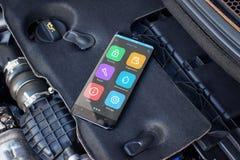 Κινητό τηλέφωνο σε μια μηχανή αυτοκινήτων με τα apps για τη διάγνωση των προβλημάτων αυτοκινήτων Στοκ Εικόνες