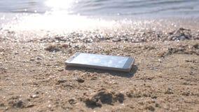 Κινητό τηλέφωνο στην αμμώδη παραλία θάλασσας με τα κύματα απόθεμα βίντεο