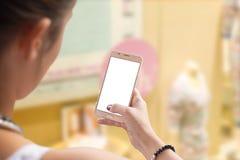 Κινητό τηλέφωνο χρήσης γυναικών για τις αγορές Στοκ Φωτογραφία