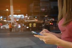 Κινητό τηλέφωνο χρήσης γυναικών, νύχτα στην πόλη στοκ φωτογραφία με δικαίωμα ελεύθερης χρήσης