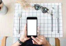 Κινητό τηλέφωνο χρήσης γυναικών apps στον πίνακα εστιατορίων κινητή πληρωμή δ Στοκ φωτογραφίες με δικαίωμα ελεύθερης χρήσης