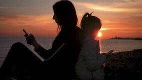 Κινητό τηλέφωνο χρήσης μητέρων και κορών σκιαγραφιών στην παραλία στο ηλιοβασίλεμα Έννοια της τεχνολογίας, τρόπος ζωής φιλμ μικρού μήκους