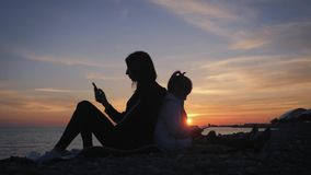 Κινητό τηλέφωνο χρήσης μητέρων και κορών σκιαγραφιών στην παραλία στο ηλιοβασίλεμα Έννοια της τεχνολογίας, τρόπος ζωής απόθεμα βίντεο
