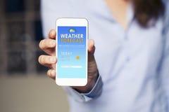 Κινητό τηλέφωνο app πρόγνωσης καιρού σε μια οθόνη συσκευών gesturing γυναίκα μανικιούρ χεριών Στοκ Φωτογραφίες