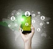 Κινητό τηλέφωνο εκμετάλλευσης χεριών με την πράσινη οθόνη Στοκ Φωτογραφία