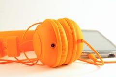 Κινητό τηλέφωνο και πορτοκαλιά ακουστικά Στοκ Φωτογραφίες