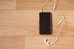 Κινητό τηλέφωνο με τα άσπρα ακουστικά Στοκ φωτογραφία με δικαίωμα ελεύθερης χρήσης