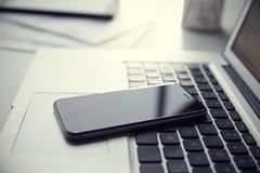 Κινητό τηλέφωνο που στηρίζεται στο πληκτρολόγιο lap-top Στοκ Εικόνα