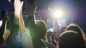 Κινητό τηλέφωνο στα αυξημένα χέρια των ανθρώπων στο υπόβαθρο των φω'των σκηνών, συσκευή στα αυξημένα όπλα του θαυμαστή στη συναυλ φιλμ μικρού μήκους