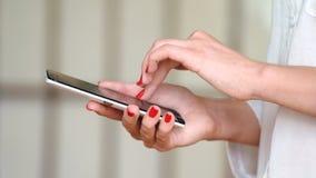 Κινητό τηλέφωνο χρήσης νέων κοριτσιών για τα κοινωνικά δίκτυα ξεφυλλίσματος φιλμ μικρού μήκους