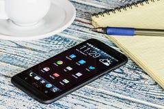 Κινητό τηλέφωνο HTC με αρρενωπές εφαρμογές στον υπολογιστή γραφείου Στοκ φωτογραφία με δικαίωμα ελεύθερης χρήσης