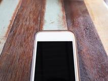Κινητό smartphone στο ξύλινο επιτραπέζιο υπόβαθρο Στοκ φωτογραφία με δικαίωμα ελεύθερης χρήσης