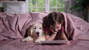 Κινούμενα σχέδια προσοχής μικρών κοριτσιών με το κουτάβι στο κρεβάτι απόθεμα βίντεο
