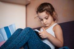 Κινούμενα σχέδια προσοχής μικρών κοριτσιών στην ταμπλέτα στοκ εικόνα με δικαίωμα ελεύθερης χρήσης