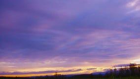 Κινούμενα σύννεφα χρονικού σφάλματος στο ηλιοβασίλεμα πέρα από την πράσινη χλόη απόθεμα βίντεο