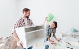 Κινούμενες επιπλώσεις ζεύγους στο καινούργιο σπίτι τους στοκ φωτογραφία