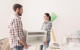 Κινούμενες επιπλώσεις ζεύγους στο καινούργιο σπίτι τους στοκ εικόνες με δικαίωμα ελεύθερης χρήσης