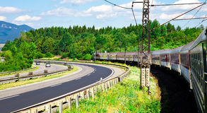 Κινούμενες τραίνο και εθνική οδός ενάντια στα βουνά Στοκ Φωτογραφία