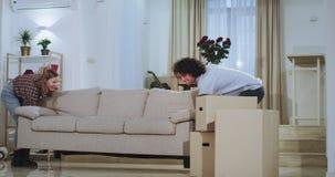 Κινούμενη ημέρα για το ελκυστικό νέο ζεύγος που φέρνουν τον καναπέ στη μέση ενός ευρύχωρου καθιστικού ευτυχούς αυτοί απολαμβάνουν απόθεμα βίντεο