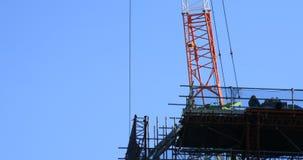 Κινούμενοι γερανοί πίσω από το μπλε ουρανό στην κατώτερη κατασκευή απόθεμα βίντεο