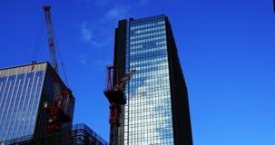 Κινούμενοι γερανοί πίσω από το μπλε ουρανό στο κτίριο γραφείων απόθεμα βίντεο