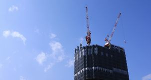Κινούμενοι γερανοί στην κατώτερη κατασκευή πίσω από το μπλε ουρανό στο Τόκιο απόθεμα βίντεο