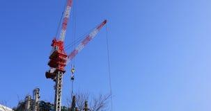 Κινούμενοι γερανοί στην κατώτερη κατασκευή πίσω από το μπλε ουρανό στο Τόκιο φιλμ μικρού μήκους