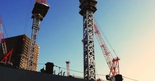 Κινούμενοι γερανοί στην κατώτερη κατασκευή σε Ariake Τόκιο στο σούρουπο απόθεμα βίντεο