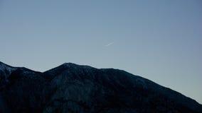 Κινούμενο αεριωθούμενο αεροπλάνο πέρα από το βουνό Στοκ Εικόνες