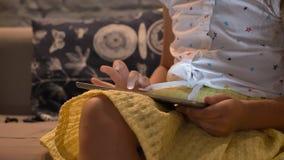 Κινούμενο μήκος σε πόδηα των παίζοντας παιχνιδιών μικρών κοριτσιών στην ταμπλέτα και του καθίσματος στον καναπέ, παιδί που χρησιμ φιλμ μικρού μήκους