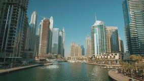 Κινούμενο πανόραμα από τη γέφυρα στη μαρίνα του Ντουμπάι στην ηλιόλουστη ημέρα, αντανάκλαση από το νερό φιλμ μικρού μήκους