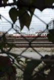 Κινούμενο τραίνο που πυροβολείται μέσω ενός φράκτη στοκ εικόνες