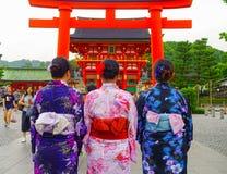 ΚΙΟΤΟ, ΙΑΠΩΝΙΑ - 5 ΙΟΥΛΊΟΥ 2017: Νέοι τουρίστες που δίνουν μια πλάτη, που επισκέπτεται έναν ναό inari fushimi στη βροχερή ημέρα σ Στοκ Φωτογραφίες