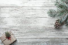 Κλάδοι δέντρων έλατου Χριστουγέννων με το κιβώτιο δώρων στο άσπρο αγροτικό ξύλινο υπόβαθρο Στοκ φωτογραφία με δικαίωμα ελεύθερης χρήσης