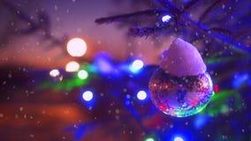 Κλάδοι κινηματογραφήσεων σε πρώτο πλάνο του χριστουγεννιάτικου δέντρου με τα ζωηρόχρωμα να αναβοσβήσει φω'τα bokeh που περιβάλλετ φιλμ μικρού μήκους